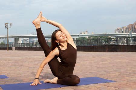 Pretty woman doing yoga exercises in the park Portrait Imagens