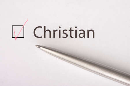 Christian - checkbox with a tick on white paper with metal pen. Checklist concept. Close-up