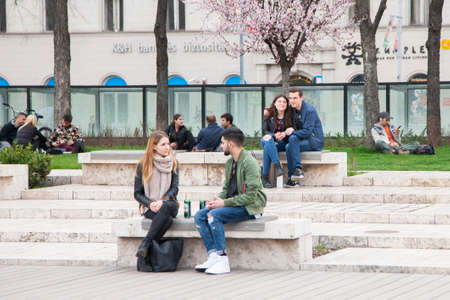 Budapest, Hungary - April 5, 2018: Two young people sitting on benches in a park and talking Genre Editorial