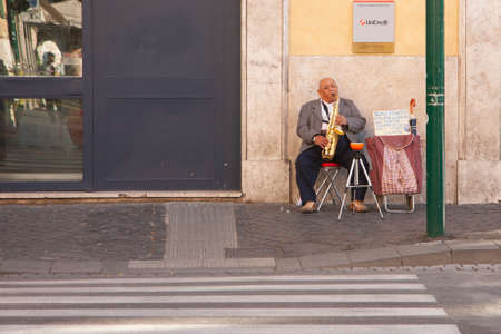 Rome, Italy, October 9, 2011: Elderly man plays saxophone at the entrance to the bank Genre Editorial