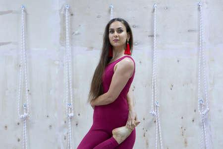 Young woman practicing yoga vrikshasana in gym. Yoga concept. Portrait Banque d'images