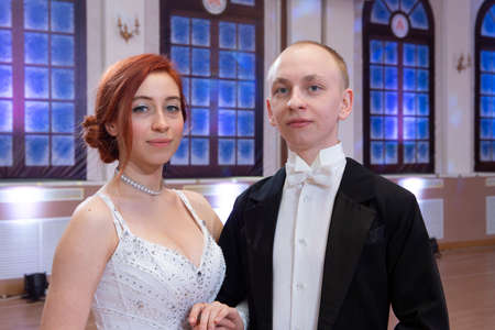 Young good looking couple in evening dress and dress coat posing in elegant way in a classical style Portrait Stockfoto