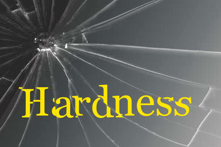 The text Hardness on the broken glass. Background