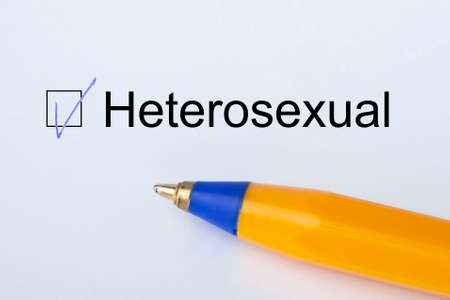 Heterosexual - checkbox with a tick on white paper with yellow pen. Checklist concept. Close-up
