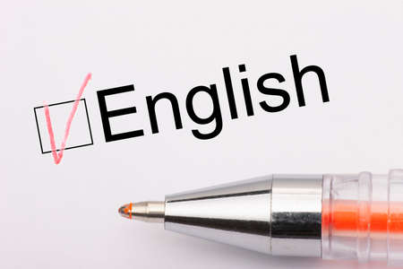 English - checkbox with a tick on white paper with metal pen. Checklist concept. Close-up