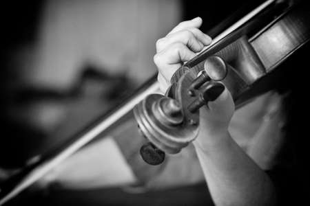 Young beautiful woman violin player looking at camera over instrument on her shoulder holding bow. Black and white image Close-up