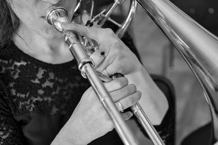 Hands of a girl playing the trombone Black and white image Close up