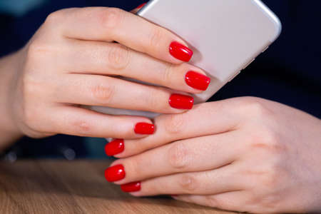 close-up, female hands with red manicure use a smartphone on a white background. Limited depth of field Close-up Reklamní fotografie - 121418723