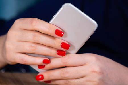 close-up, female hands with red manicure use a smartphone on a white background. Limited depth of field Close-up Reklamní fotografie