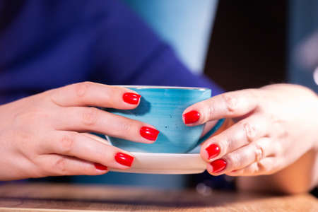 Beautiful woman hands with red manicure and cup Limited depth of field Close-up