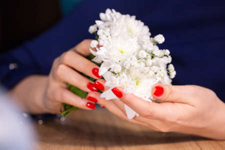 Portrait of girls manicured hands holding small cute flower bouquet Limited depth of field Close-up