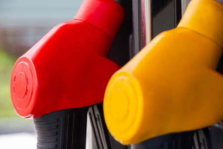 Close-up fuel nozzles on petrol and diesel fuel. Gas station pump. Man refueling gasoline with fuel in a car, holding a nozzle. Limited depth of field. Blurred image Stock Photo