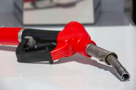 Gasoline pistol pump fuel nozzle Gas station pump. Man refueling gasoline with fuel in a car, holding a nozzle. Limited depth of field. Blurred image Close-up