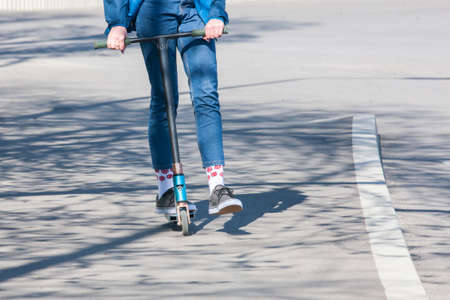 The legs of an unknown girl in white sneakers and tight jeans ride on a black electric scooter over a dark urban asphaltClose-up.