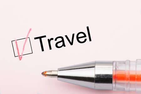 Travel - checkbox with a cross on white paper with pen. Checklist concept. Close-up