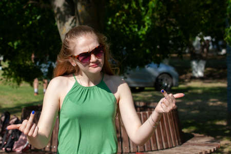 Cheerful girl making gun shot gesture. girl showing middle finger offensive gesture. Woman showing a fuck you off sign. negative expression Gesturing concept Portrait Reklamní fotografie