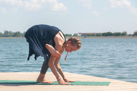 Beautiful woman practicing Yoga by the lake Portrait