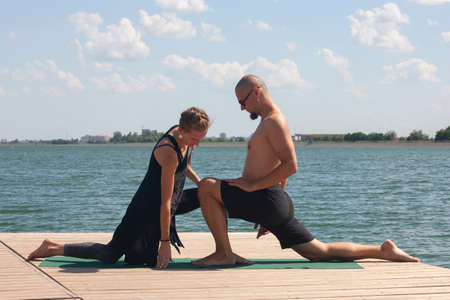 Happy couple doing yoga beside the water at the beach Portrait
