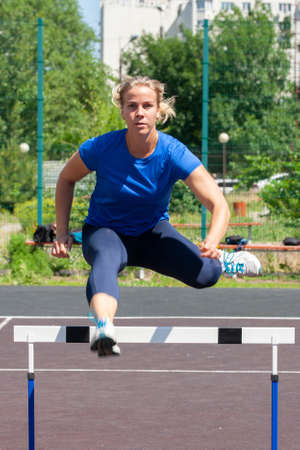 A beautiful and athletic girl is running hurdles in the stadium Porttait