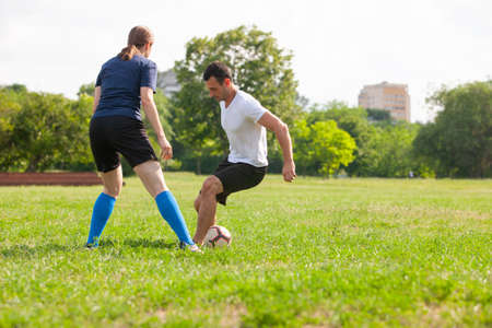 Femme de joueur de football glissant s'attaquer à la balle de son adversaire sur le terrain de football au stade Soccer