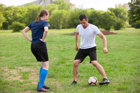 Football player woman sliding tackle the ball from his opponent on football field at stadium Soccer