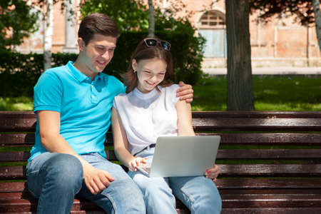 Young handsome couple using notebook in the public park Portrait Stock Photo - 124686305