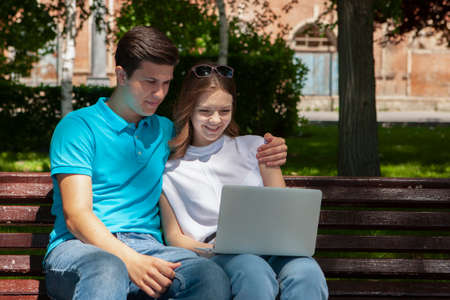 Young handsome couple using notebook in the public park Portrait Stock Photo - 124683797