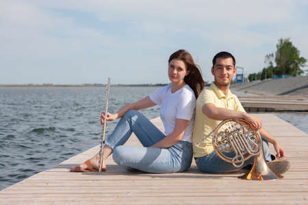 The guy playing the horn and the girl playing the flute on the lake Portrait