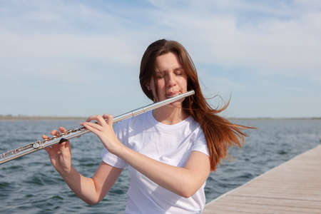 A beautiful woman posing in beach while playing on a flute. Portrait