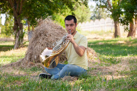 French horn player playing music instrument Man hornist classical musician Portrait Standard-Bild