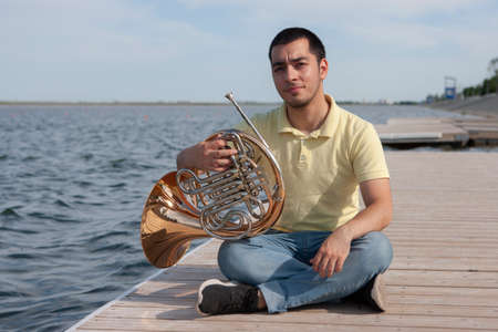 Portrait of teen musician playing instrument classic french horn. Close-up Stock Photo