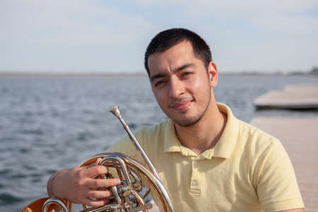 Portrait of teen musician playing instrument classic french horn. Close-up Standard-Bild