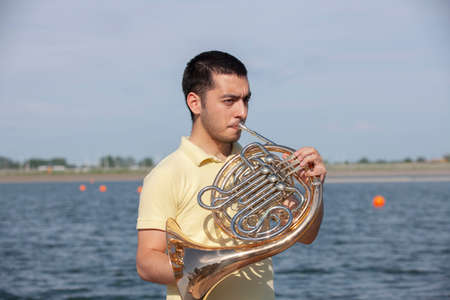 French horn player playing music instrument Man hornist classical musician Portrait Stock Photo