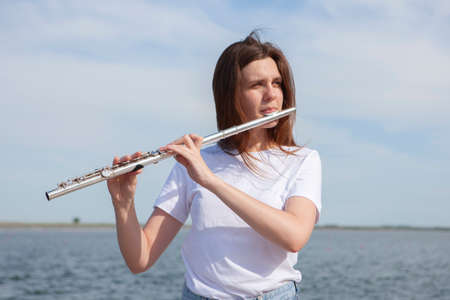 Beautiful woman playing flute in Waterfront Smiling woman. Portrait