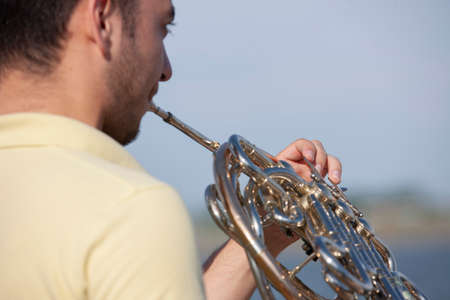 French horn instrument. Player hands playing horn music brass instrument Portrait