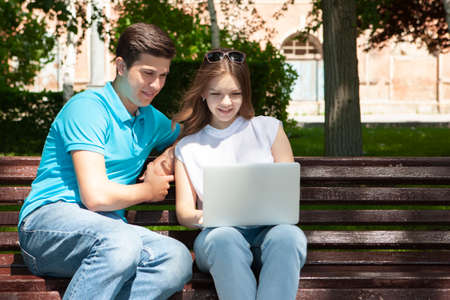 Young handsome couple using notebook in the public park Portrait Stock Photo - 124686557