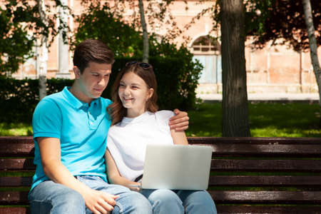 Young handsome couple using notebook in the public park Portrait Stock Photo - 124686555