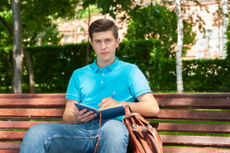 Young man university student online learning via laptop computer, sitting on a bench on a campus. Portrait