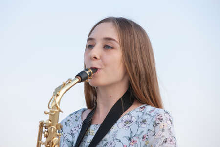 Young woman with saxophone with nature background. Portrait 免版税图像