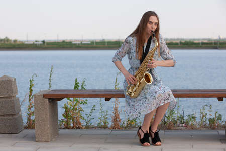 Young woman with saxophone with nature background. Portrait Stock Photo