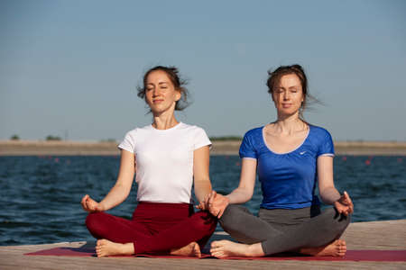 Two young women doing yoga at nature. Fitness, sport, yoga and healthy lifestyle concept - group of people making yoga pose on lake pier at sunset. Portrait