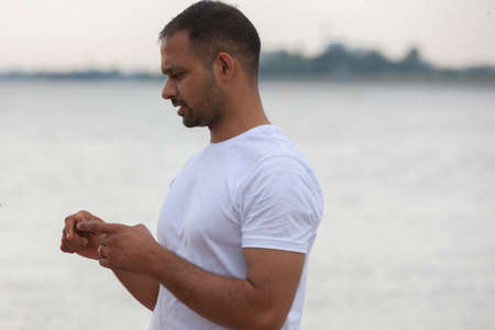 fitness, sport, yoga and healthy lifestyle concept - close up of people meditating in easy sitting pose on river or lake berth. Portrait