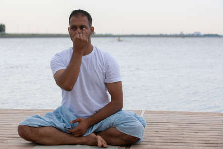 Profile shot of mature man meditating in lotus position on pier against lake Portrait