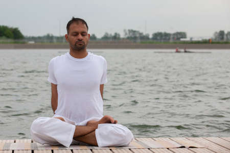 Young man doing yoga and meditating in warrior pose on beach Portrait Imagens