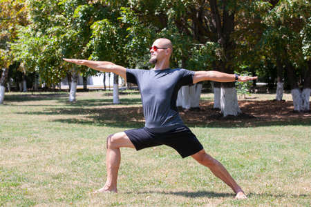 Man exercising in park. Smiling caucasian male doing core workout on grass. Portrait
