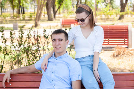 beautiful young couple sitting on a bench in the park. Portrait Stock Photo