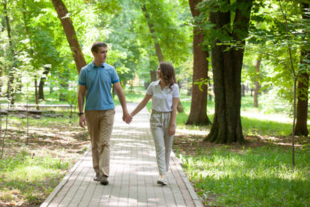 Couple walking hand in hand in a park - Romantic date outdoors. Portrait 免版税图像
