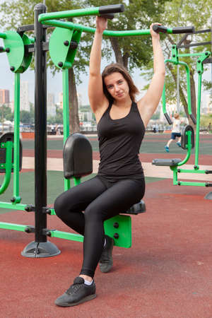 woman exercising with exercise equipment in the public park. Woman in a sports simulator training on the playground. Portrait