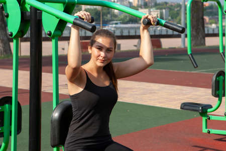 Young, fit and sporty girl training in outdoor gym. Fitness, sport and healthy lifestyle. Portrait Stock Photo