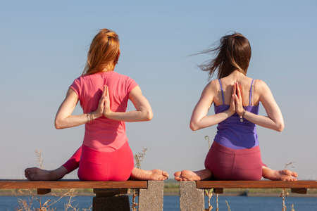 two adult women aged yoga outdoors in summer in the park. Portrait